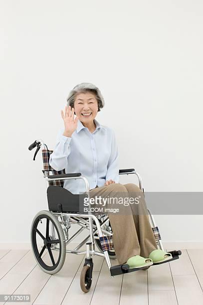 Senior woman in wheelchair waving, smiling