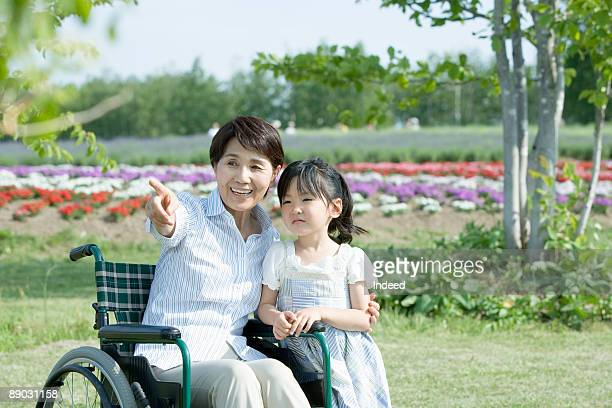 Senior woman in wheelchair with granddaughter