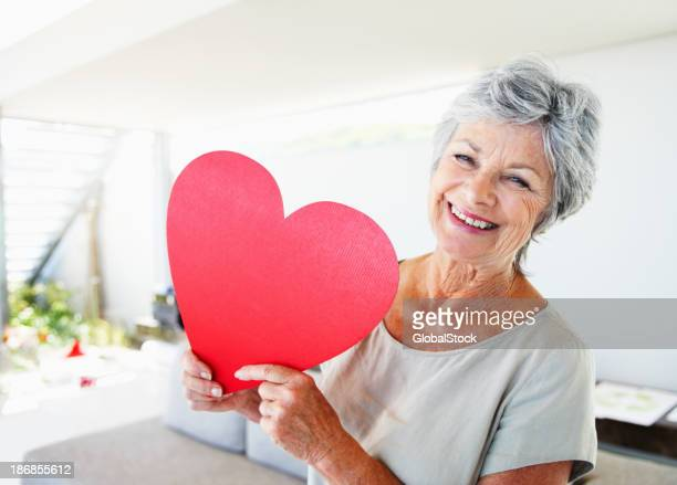 Senior woman in white shirt holding a large paper heart