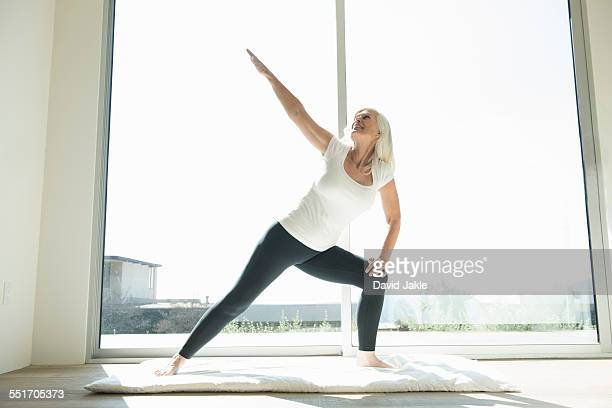 Senior woman in yoga pose, arm raised