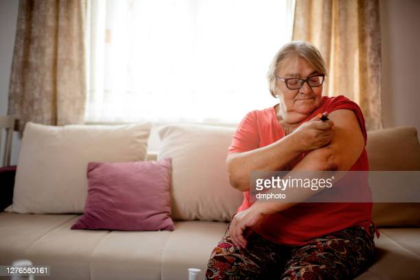 senior woman injecting insulin in hers arm - medical injection stock pictures, royalty-free photos & images