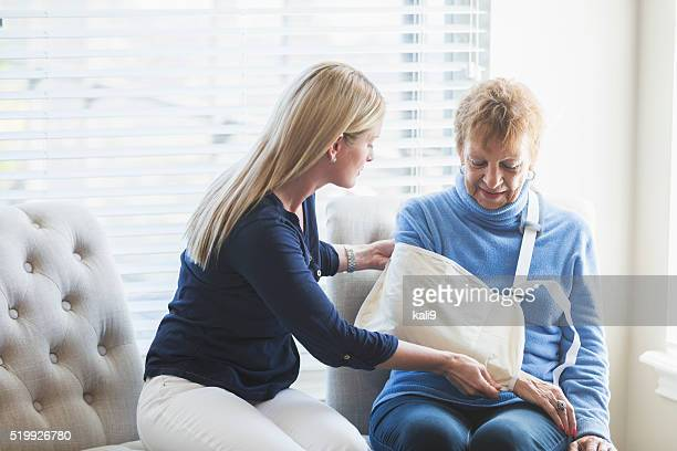 Senior woman, injury to arm, with caregiver at home
