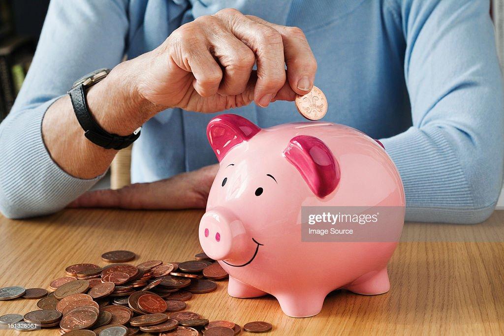Senior woman inserting coins into piggybank : Stock Photo