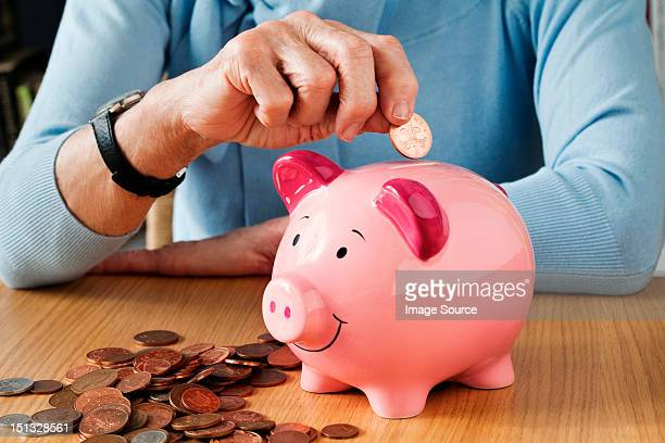 senior woman inserting coins into piggybank - piggy bank stock photos and pictures