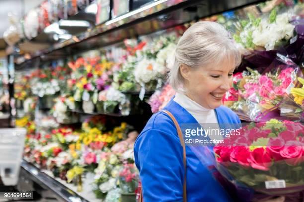 Ältere Frau inspiziert Strauß Rosen im Supermarkt