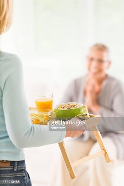 Femme âgée est servi un petit déjeuner équilibré