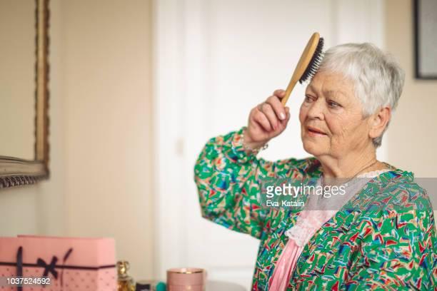 mulher sênior é pentear o cabelo de manhã - penteando - fotografias e filmes do acervo