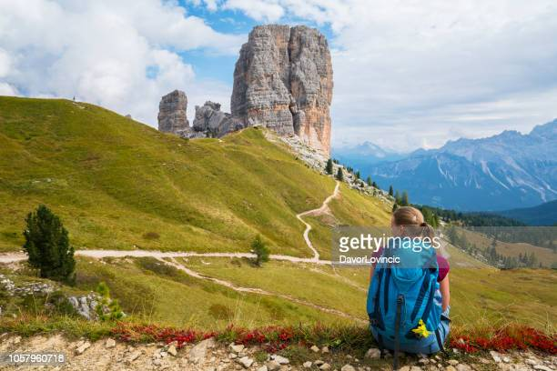 senior woman is  crouching and taking a photo of five towers (cinque torri) as mythical heart of the dolomites, italy. - cortina dampezzo foto e immagini stock