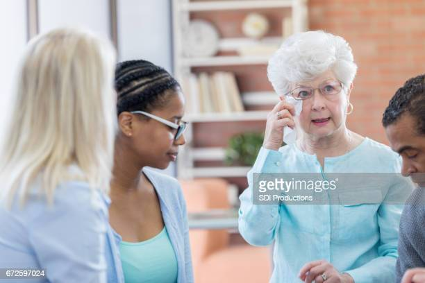 Senior woman is emotional during support group meeting