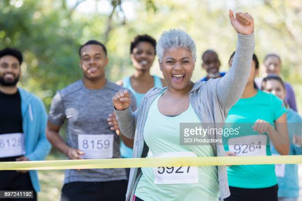 senior woman is first to cross finish line in charity race - finishing line stock pictures, royalty-free photos & images