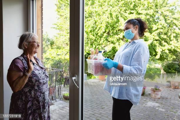 een hogere vrouw krijgt een mand met kruidenierswaren in contactloze levering tijdens tijden van coronacrisis - beschermend masker werkkleding stockfoto's en -beelden