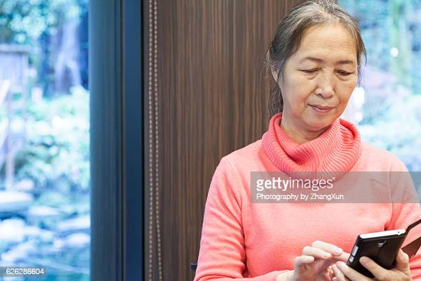 Senior woman is operating mobile phone in the room.