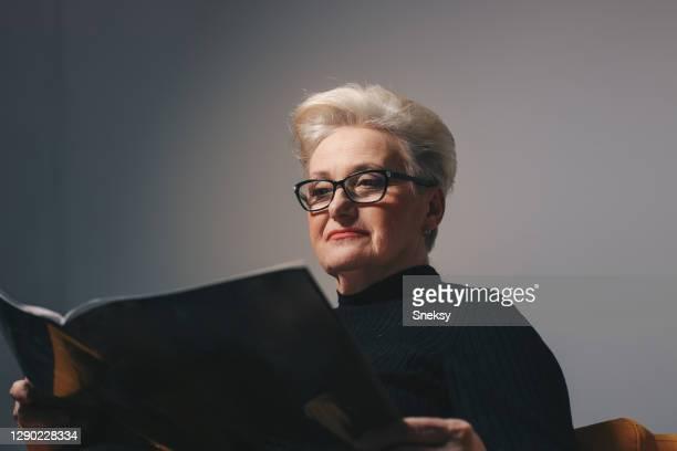 la femme aînée lit le magazine. plan rapproché. - lunettes de lecture photos et images de collection