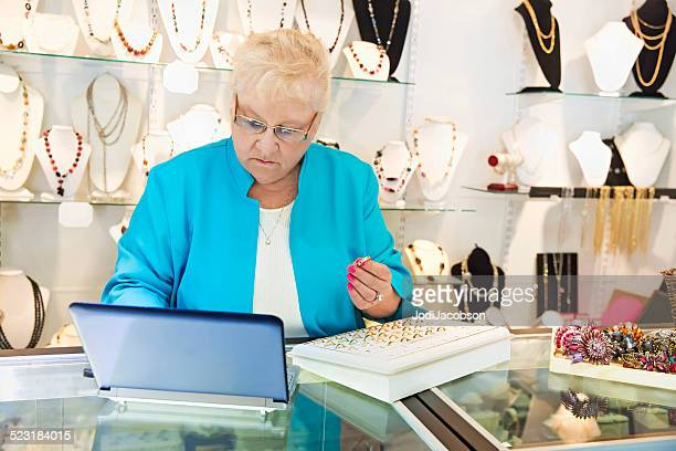 senior woman jewelry store owner ordering merchandise on line - jeweller stock pictures, royalty-free photos & images