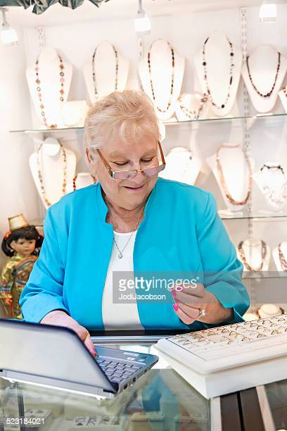 Senior woman jewelry store owner ordering rings on her computer