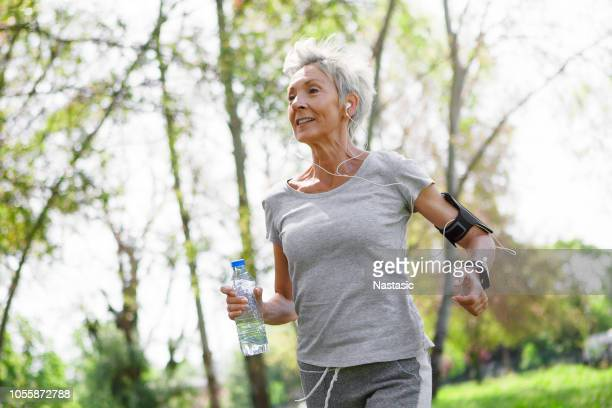 senior woman jogging in park wearing smart watch and smart phone - center athlete stock pictures, royalty-free photos & images