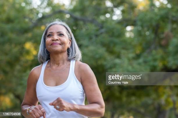 mujer mayor corriendo en el parque público - ejercicio físico fotografías e imágenes de stock