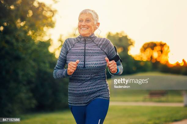 senior woman jogging in the park - watch what happens: live stock pictures, royalty-free photos & images