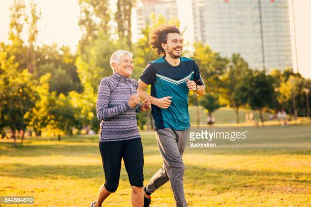Senior woman jogging with a personal trainer outdoors