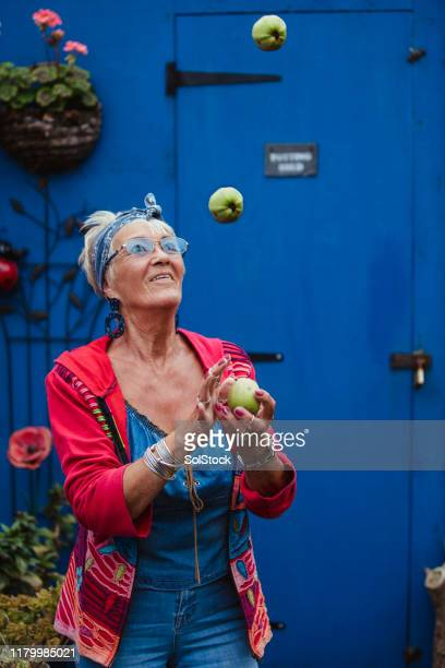 senior woman juggling apples - showus stock pictures, royalty-free photos & images