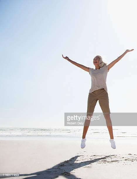 senior frau springen am strand - arme hoch stock-fotos und bilder