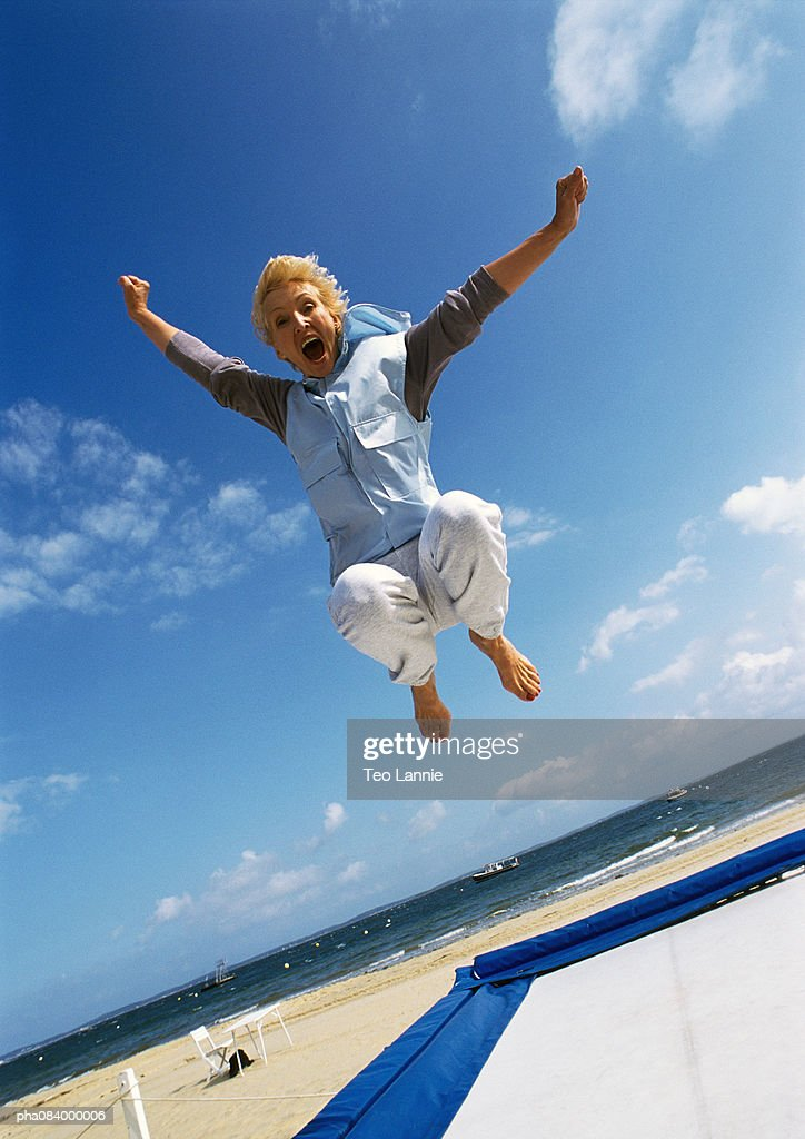 Senior woman jumping on trampoline at beach. : Stockfoto