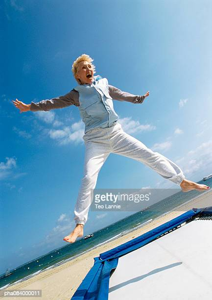 senior woman jumping on trampoline at the beach. - one mature woman only stock pictures, royalty-free photos & images