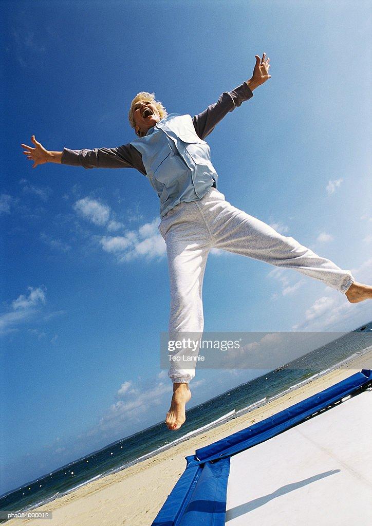 Senior woman jumping on trampoline at the beach. : Stockfoto