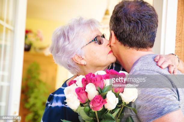 Senior woman kisses mature son bringing bouquet of roses