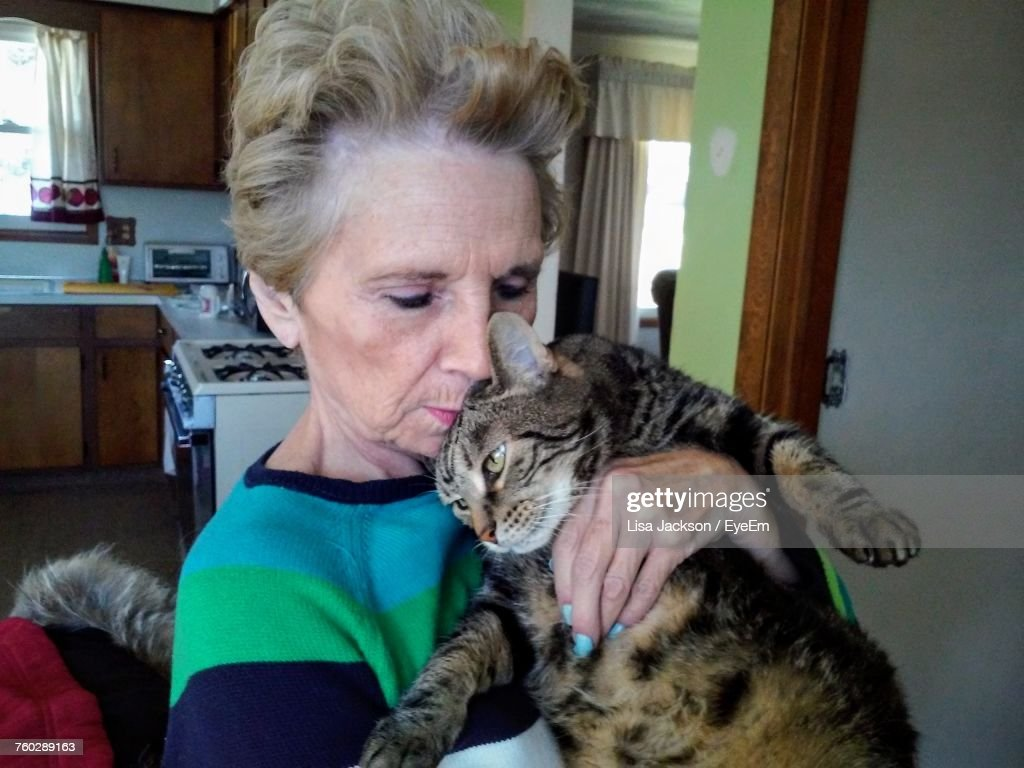 Senior Woman Kissing Cat While Standing At Home : Stock Photo
