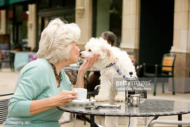 Senior woman kissing dog, sitting at cafe table