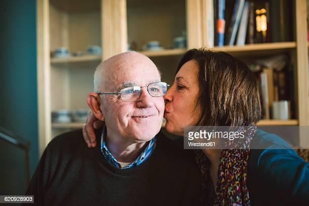 Senior woman kissing her husband at home