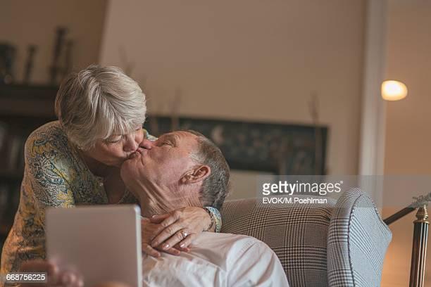 Senior woman kissing her husband holding digital tablet