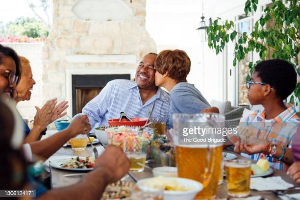 senior woman kissing husband at table during family gathering - lunch stock pictures, royalty-free photos & images