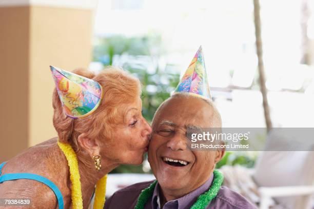 Senior woman kissing husband on birthday