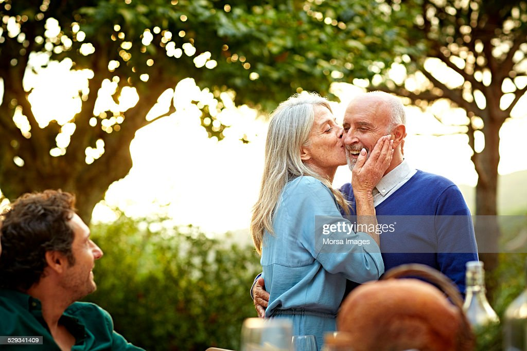 Loving senior woman kissing man on cheek during social gathering in yard