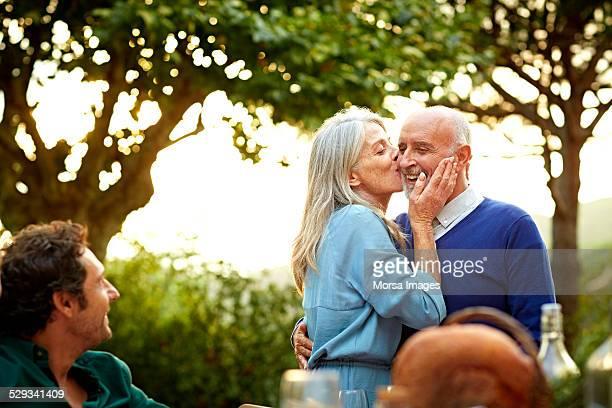 Senior woman kissing man in yard