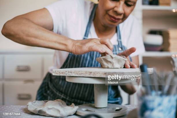 senior woman kneading clay in bowl shape at workshop - hobbies stock pictures, royalty-free photos & images