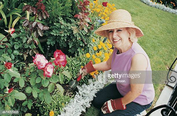 senior woman kneeling on the grass and using a garden trowel by a flowerbed - sleeveless top stock photos and pictures