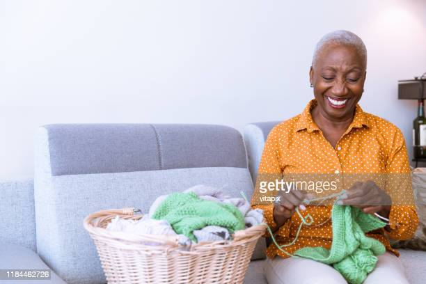 senior woman knitting at home - knitting stock pictures, royalty-free photos & images