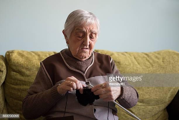 Senior woman knitting at home