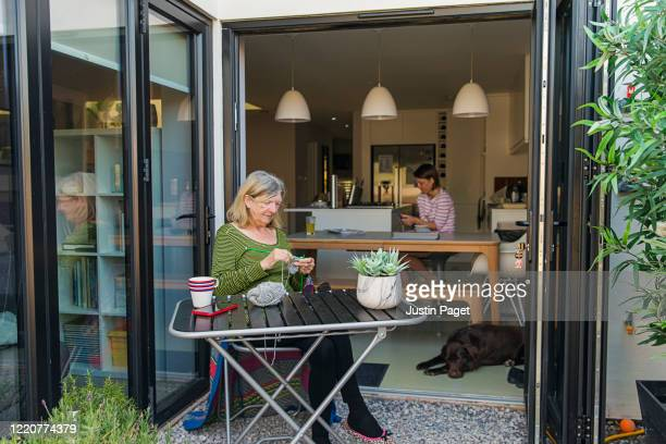 senior woman knitting in backyard. daughter is in background - shielding stock pictures, royalty-free photos & images