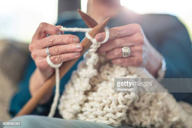 Senior woman knitting on couch at home