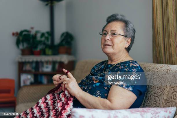 senior woman knitting - fat old lady stock photos and pictures