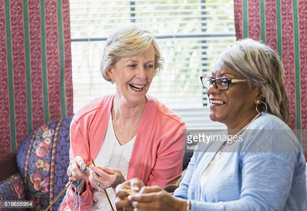 Senior woman knitting with African American friend