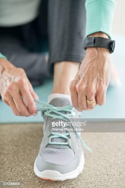 Senior woman lacing up trainer