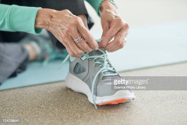senior woman lacing up trainers - tying stock pictures, royalty-free photos & images