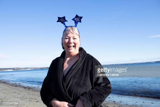 senior woman laughing at camera wearing a bathrobe at the beach on new year's day - catherine ledner stock pictures, royalty-free photos & images