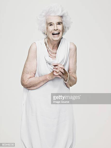 senior woman laughing - grey dress stock pictures, royalty-free photos & images
