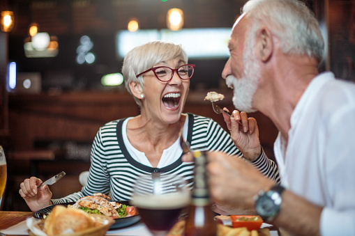Senior woman laughing while feeding her male partner in the restaurant 1015301798